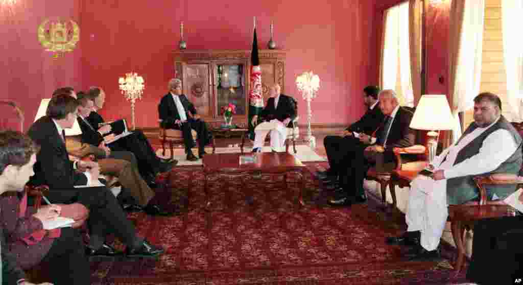 This image released by the Afghan presidential palace shows U.S. Secretary of State John Kerry talking with Afghanistan's President Hamid Karzai at the presidential palace in Kabul, July 11, 2014.