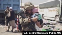 ທະຫານມາຣີນຂອງສະຫະລັດ ອຸ້ມເດັກນ້ອຍໃນລະຫວ່າງການຍົກຍ້າຍຢູ່ທີ່ສະໜາມບິນສາກົນ ຮາມິດ ຄາຣຊາຍ ໃນນະຄອນ ຫຼວງກາບູລ, ວັນທີ 28 ສິງຫາ (ພາບຂອງທະຫານມາຣີນ ຂອງສະຫະລັດ, US Marine Corps photo)