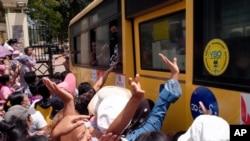 A crowd greets people aboard a bus as it leaves Insein Prison, in Yangon, Myanmar, April 17, 2021.