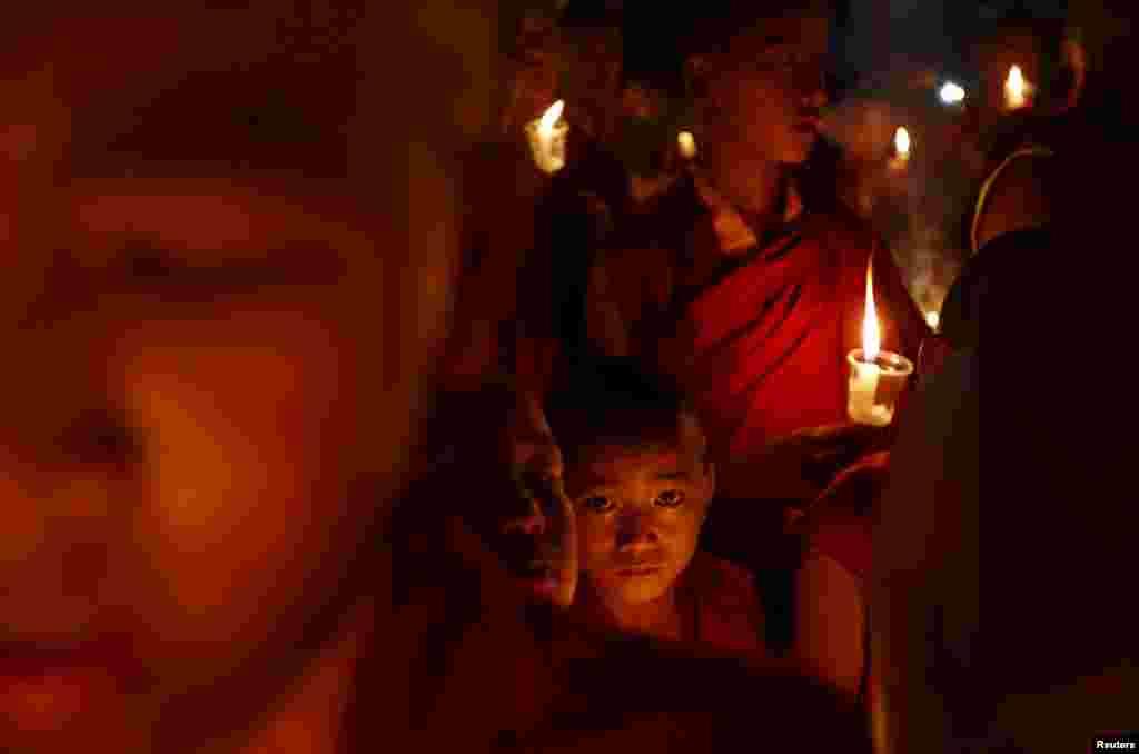 Para biksu Buddha memegang lilin dalam upacara doa mengenang korban gempa bumi di Kathmandu, Nepal.
