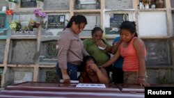 Relatives of a mudslide victim mourn over his coffin at a cemetery in Santa Catarina Pinula, on the outskirts of Guatemala City, Oct. 6, 2015.