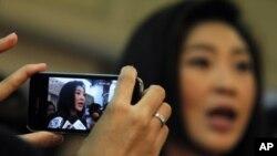 ແມ່ຍິງຄົນນຶ່ງໃຊ້ໂທລະສັບມືຖືຂອງນາງ ຖ່າຍຮູບເອົາທ່ານນາງ ຢິ່ງລັກ ຊິນນະວັດ ນາຍົກລັດຖະມົນຕີ ທີ່ຖືກເລືອກຕັ້ງໃໝ່ຂອງໄທ ຂະນະທີ່ທ່ານນາງຖະແຫລງຕໍ່ກອງປະຊຸມນັກຂ່າວ ເມື່ອວັນທີ 13 ກໍລະກົດ 2011 ທີ່ບາງກອກ. (REUTERS/Sukree Sukplang)