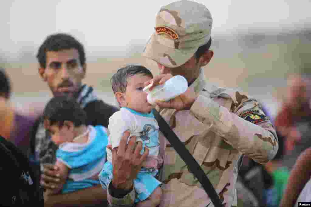 An Iraqi soldier cares for a displaced child from Ramadi at the outskirts of Baghdad, May 19, 2015.