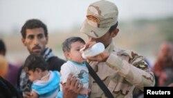 一名伊拉克士兵帮助照看一名从拉马迪逃难出来的孩子
