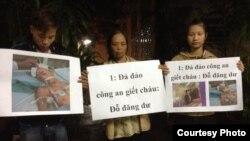 Mẹ và anh chị của nạn nhân Đỗ Đăng Dư cầm biểu ngữ phản đối. (Facebook: Dung Truong)