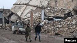 反政府武裝戰士在位於阿勒頗鄉村的阿拉伊鎮被毀壞的建築物旁行走(2016年12月30日)