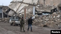 Rebel fighters walk near damaged buildings in al-Rai town, northern Aleppo countryside, Syria, Dec. 30, 2016.