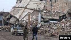 2016年12月30日,反政府战斗人员在叙利亚北部城市阿勒颇农村地带的拉伊镇毁损建筑物附近行走。