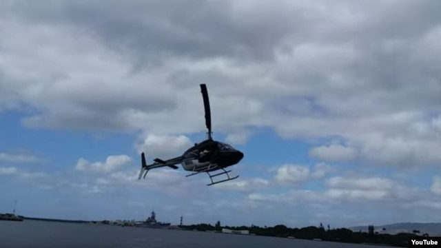 A screengrab from YouTube video showns a Bell 206 helicopter as it goes down in Pearl Harbor, Hawaii, Feb. 18, 2016. (Video courtesy - Shawn Winrich)