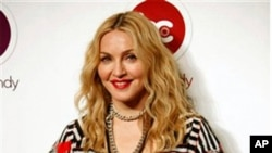 Madonna smiles as she poses for pictures during the opening of Hard Candy Fitness, her new gym in Mexico City, 29 Nov. 2010