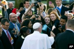 Pope Francis greets well-wishers while departing for the White House from the Apostolic Nunciature, the Vatican's diplomatic mission in Washington, Sept. 23, 2015.