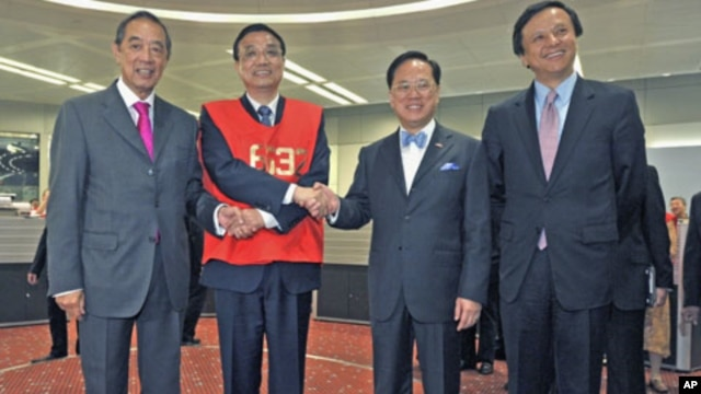 Chinese Vice Premier Li Keqiang (2nd L), wearing a floor trader's vest, poses with Hong Kong Stock Exchange Chairman Ronald Arculli (L), Chief Executive Charles Li (R) and Hong Kong Chief Executive Donald Tsang during his visit to the Hong Kong Stock Exch