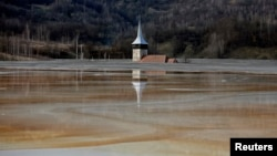 FILE - The old church of Geamana village is partially submerged by polluted water tainted with cyanide and other chemicals near Rosia Montana, central Romania, March 24, 2014.