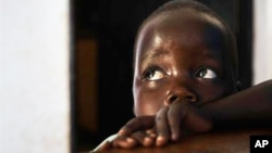 """In this photo taken Friday, April 27, 2012, in Gulu, Uganda, Betty, 3, looks up at her mother Adye Sunday, 25, unseen, who was abducted when she was 13 by Lord's Resistance Army leader Joseph Kony and forced to be one of his dozens of """"wives."""" She says he's also the father of her two children"""