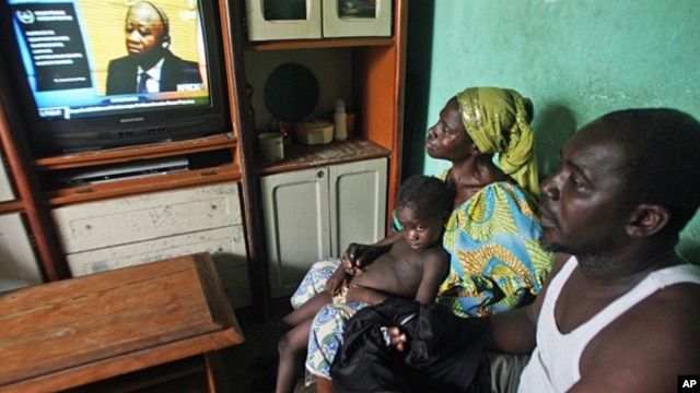 Adama Fofana,  who says two of his brothers were killed in post-election violence and their bodies dumped in a mass grave, watches the televised trial of former Ivorian President Laurent Gbagbo, Feb. 19, 2013.