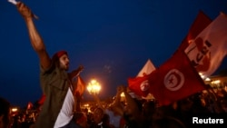 An anti-government protester shouts slogans as others wave flags and signs during a demonstration at Kasbah Square where the government headquarters are located, to call for the departure of the Islamist-led ruling coalition, in Tunis, Aug. 31, 2013.