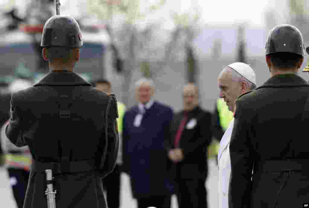 Pope Francis walks past the honor guard as he arrives at the Esenboga airport in Ankara, Friday, Nov. 28, 2014.