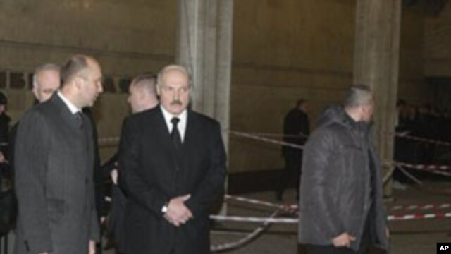Belarus President Alexander Lukashenko, center, accompanied by his bodyguards, looks at the blast site inside the Oktyabrskaya subway station in Minsk, Belarus,  April 11, 2011