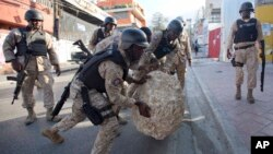 Kèk manm Polis Nasyonal d Ayiti (PNH) ap wete wòch ki te bare yon lari apre yon manifestasyon opozisyon an te mete sou pye.