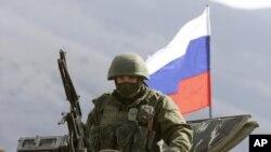 Солдат без розпізнавальних знаків на тлі російського прапора біля української військової бази у Перевальному в Криму 15 березня 2014 р.