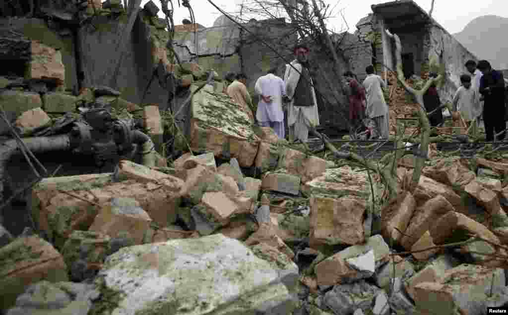 Residents stand among rubble and debris at the site of a bomb attack in Quetta, Pakistan, April 24, 2013.