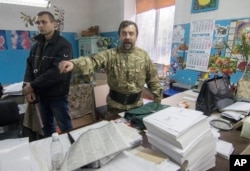 A member of a regional election commission argues during an inspection of voters ballots in a printing house in Mariupol, a major port and steel city in Ukraine's east, Oct. 25, 2015.