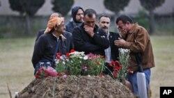 Familiares de uno de los mineros muertos junto a su tumba en Soma.