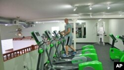 Green Microgym owner Adam Boesel on an elliptical machine that generates electricity during a workout.