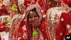 An Indian Muslim bride smiles, as she sits with other brides during a mass wedding organized by a social organization in Ahmadabad, India, Sunday, Feb. 15, 2015.