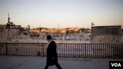 Seorang pria Yahudi Ortodoks melintasi bagian kota tua Yerusalem.