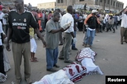 Residents prepare to carry the slain body of a woman killed during an explosion in a passenger mini-bus (matatu) in the Eastleigh neighbourhood of Kenya's capital Nairobi, November 18, 2012.