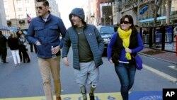 FILE - Boston Marathon bombing survivor Jeff Bauman, center, walks over the marathon finish line on the third anniversary of the bombings, April 15, 2016, in Boston.