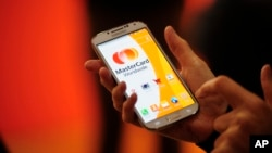 FILE - A woman uses the system Masterpass for payment with phones at the Mobile World Congress, the world's largest mobile phone trade show in Barcelona, Spain, Feb. 25, 2014.