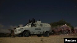 FILE - AMISOM soldiers rest atop armored vehicle during break on street patrol with local police, Mogadishu, Nov. 14, 2013.