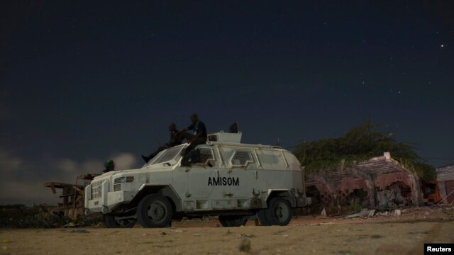 FILE - African Mission in Somalia (AMISOM) soldiers rest on top of an armored vehicle during a break on a street patrol with local police at the old stadium in  Mogadishu, Somalia, Nov. 14, 2013.