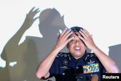 Malaysia's Royal Police Chief Khalid Abu Bakar demonstrates to the media during a news conference regarding the apparent assassination of Kim Jong Nam, the half-brother of the North Korean leader, at the Malaysian police headquarters in Kuala Lumpur, Malaysia, Feb. 22, 2017.