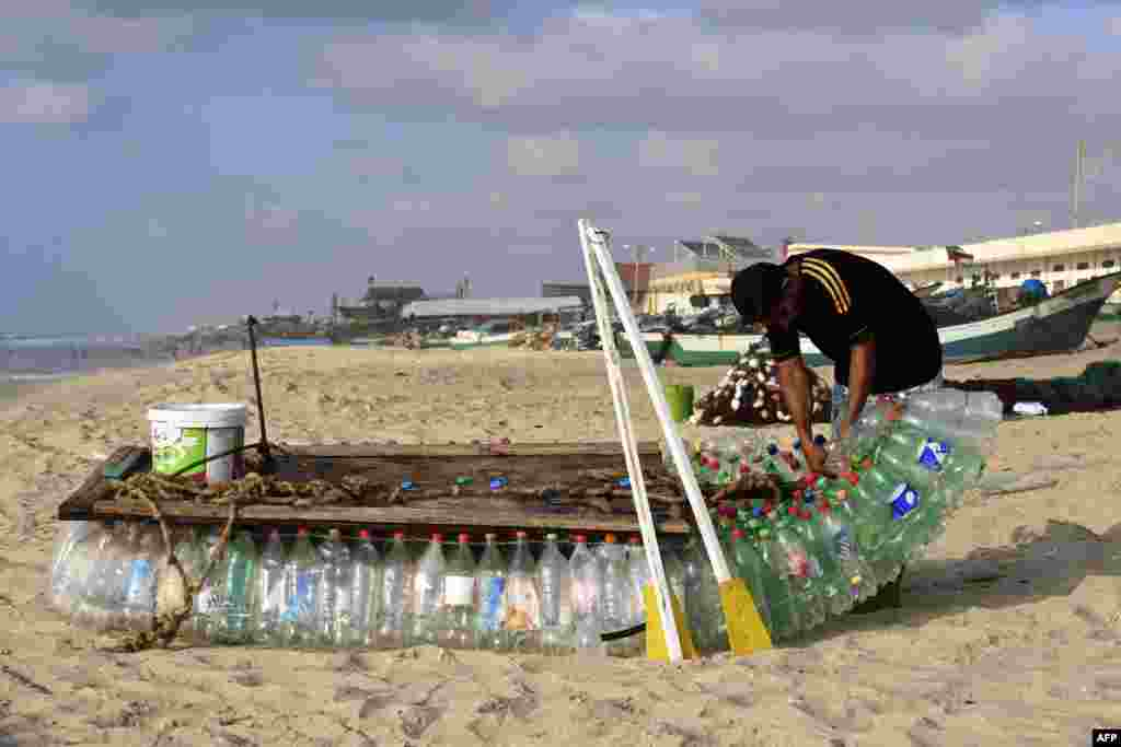 Palestinian fisherman Mouad Abu Zeid repairs his boat that he made of 700 Plastic empty bottles on a beach in Rafah in the southern Gaza Strip on August 14, 2018.