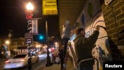 Un residente de Ferguson pinta un mural luego de dos noches de protestas por la decisión del Gran Jurado en el caso de Michael Brown.