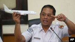 FILE - National Transportation Safety Committee investigator Nurcahyo Utomo holds a model airplane during a press conference on the committee's preliminary findings of the crash of Lion Air flight 610, in Jakarta, Indonesia, Nov. 28, 2018.