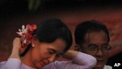 មេដឹកនាំចលនាលទ្ធិប្រជាធិបតេយ្យភូមា លោកស្រី Aung San Suu Kyi សៀតផ្កាដែលអ្នកគាំទ្រម្នាក់បានជូន ជាប់នឹងសក់ នៅក្រោយពេលលោកស្រីត្រូវបានដោះលែងពីការឃុំឃាំងក្នុងផ្ទះក្នុងទីក្រុងរ៉ង់ហ្គូនប្រទេសភូមាកាលពីថ្ងៃទី១៣ខែវិច្ឆិក