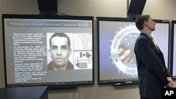 "Joel Cohen (R), with the Department of Homeland Security stands next to a giant monitor displaying Ahmed Ressam, the so-called ""Millennium Bomber,"" at the Los Angeles Joint Regional Intelligence Center in Norwalk, California, July 2006. (file photo)"