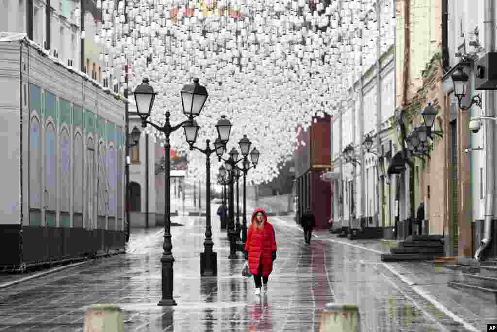 A woman walks through an almost empty street in Moscow, Russia. President Vladimir Putin ordered most Russians to stay off work until the end of April as part of a partial economic shutdown to slow the spread of the coronavirus.