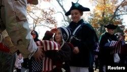 11일 미국 매사추세츠 주에서 열린 '재향군인의 날' 행사에서 퇴역하는 해군 장병(왼쪽)이 성조기를 받아들고 있다.