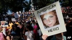 Противник консерваторов держит плакат с изображением Хизер Хейер во время митинга «Свобода слова» в Бостоне, 19 августа 2017 года