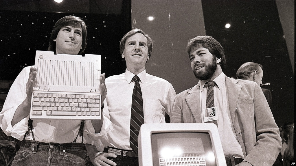 ARCHIVO - En esta foto de archivo del 24 de abril de 1984, Steve Jobs, presidente de Apple Computers, John Sculley, centro, presidente y CEO, y Steve Wozniak, cofundador de Apple, presentan la nueva computadora Apple IIc en San Francisco . Apple cumplió 40 años, y es una compañía muy diferente de la audaz startup que Jobs y Wozniak lanzaron en un garaje de Silicon Valley en 1976. (AP Photo / Sal Veder, Archivo).