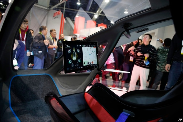 FILE - People crowd around the EHang 184 autonomous aerial vehicle at the EHang booth at CES International in Las Vegas, Jan. 6, 2016. The drone is large enough to fit a human passenger,