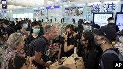 Putnici se raspravljaju sa demonstrantima dok pokušavaju da prođu kroz aerodromske odlazne gejtove, na međunarodnom aerodromu u Hong Kongu, 13. avgusta 2019.