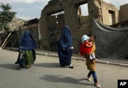 Perempuan Afghanistan dengan burqa dan anak-anak berjalan di jalan di Kabul, Afghanistan, Minggu, 22 Agustus 2021. (Foto: AP)