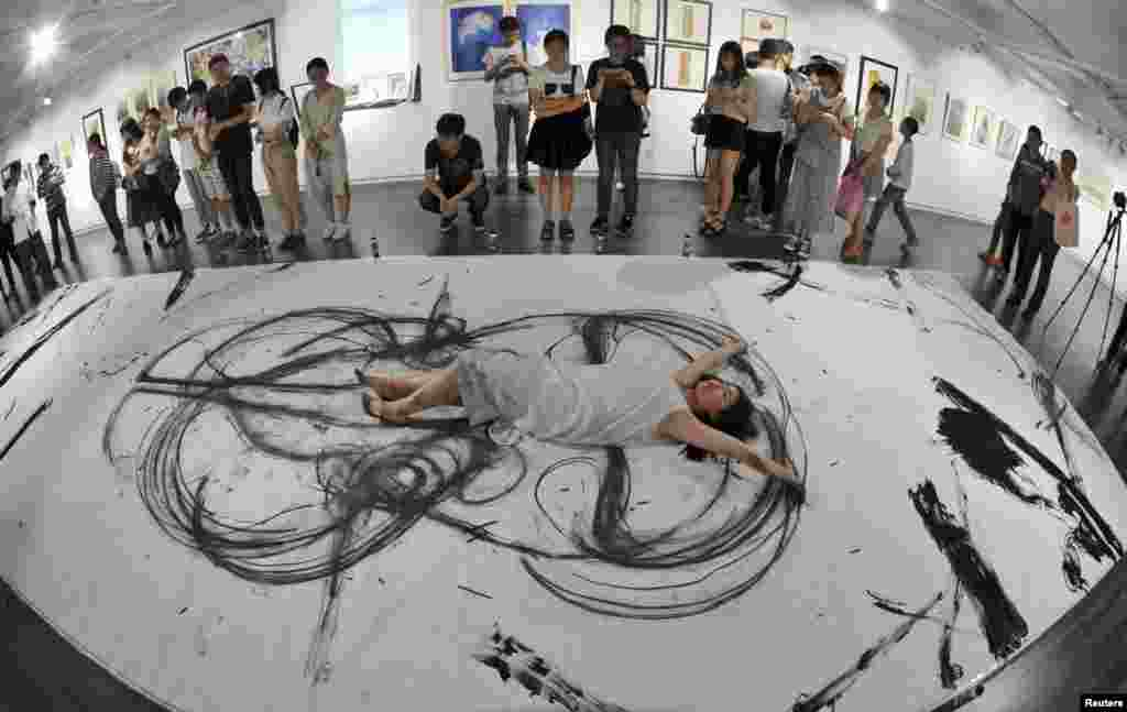 An art student lies on a giant canvas as she paints with her limbs at an exhibition of the faculty of the Hubei Institute of Fine Arts, in Wuhan, Hubei province, China.