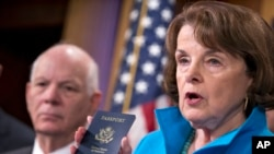 Senate Intelligence Committee Vice Chair Sen. Dianne Feinstein (r) joined by Sen. Ben Cardin, left, points to the embedded chip in her passport that contains digital information, as she and other Democrats talk about security measures for Syrian refugees and others coming into the U.S., Nov. 19, 2015, during a news conference on Capitol Hill in Washington.